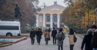 Люди идут по аллее молодежи во время осенних холодов в Бишкеке. Архивное фото