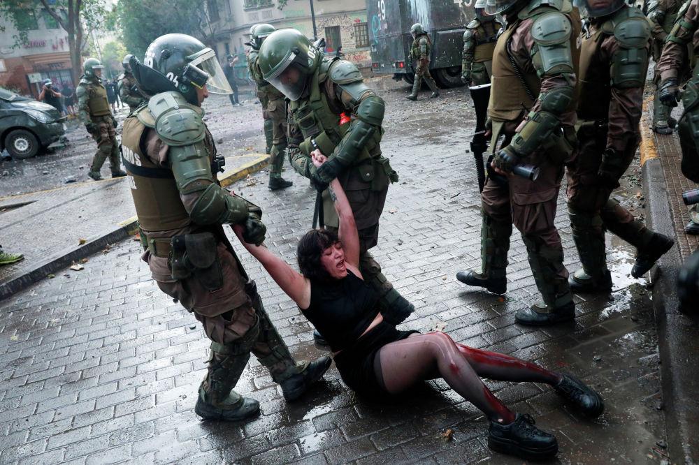 Сотрудники сил безопасности задерживают раненного демонстранта во время акции протеста против правительства Чили в Сантьяго. Чили, 4 ноября 2019 года