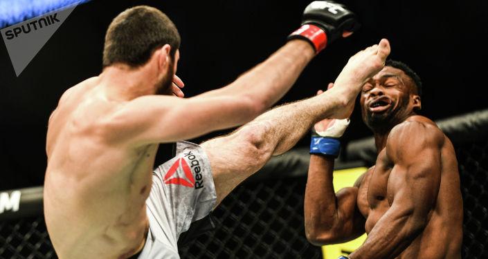 Магомед Анкалаев (Россия) и Дальча Лунгиамбула (ЮАР) (справа) во время боя в полутяжелом весе на турнире по смешанным единоборствам UFC Fight Night в Москве.