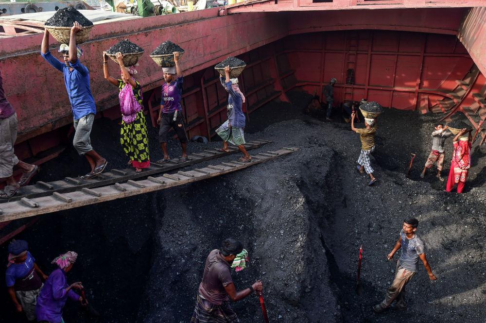 Рабочие выгружают уголь с корабля в Бангладеш.