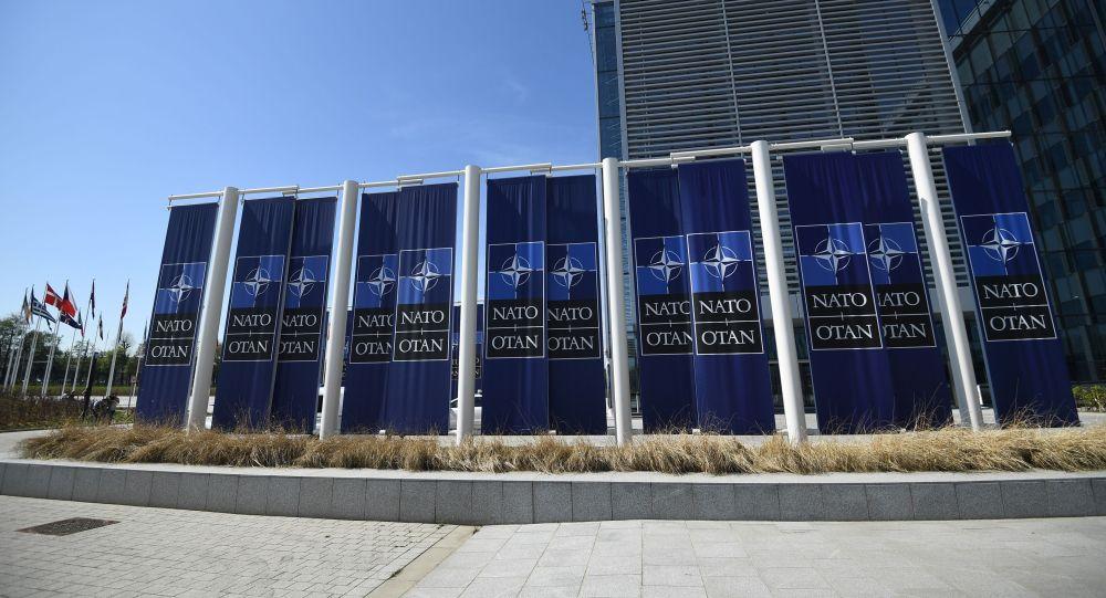 Баннеры с логотипом НАТО изображены перед новой штаб-квартирой НАТО во время пресс-тура объектов, поскольку организация перемещается из своей старой штаб-квартиры в новое здание в Брюсселе. 19 апреля 2018 года