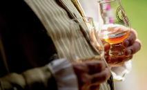 Мужчина с бокалом виски на руках. Архивное фото