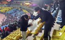 Болельщик сдает сидушки для милиционера после матча между сборными Кыргызстана и Японии на стадионе Омурзакова в Бишкеке