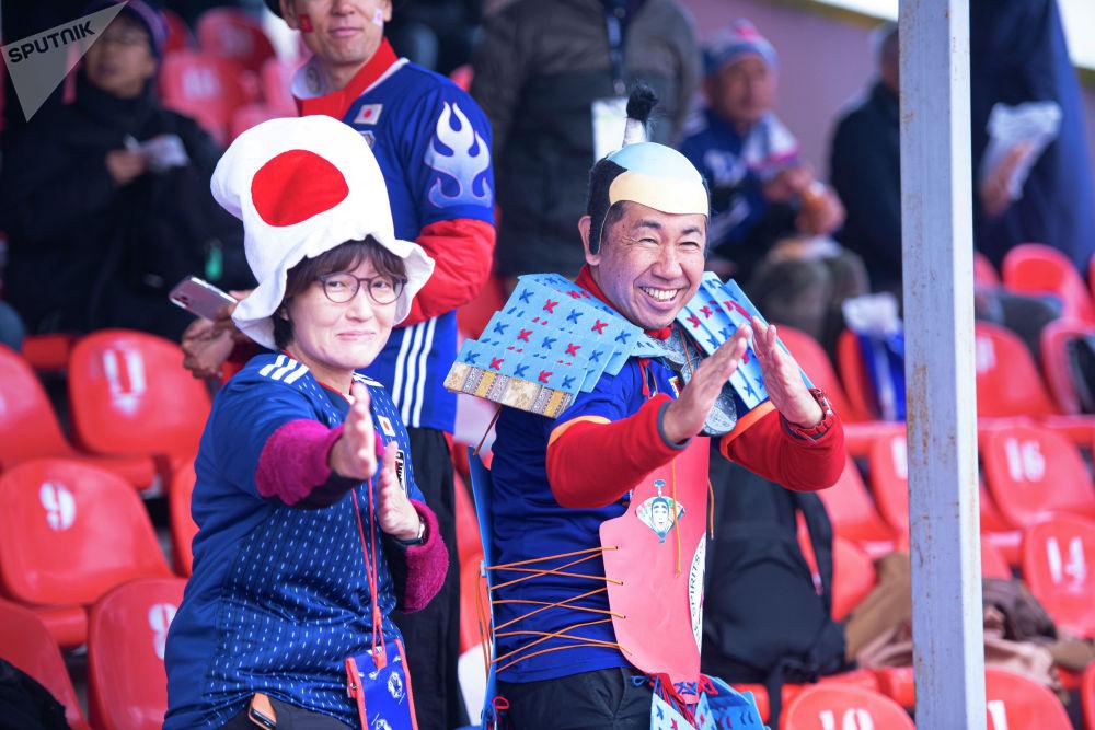 Это фанаты сборной Японии в необычном одеянии. Они веселые и приветливые.