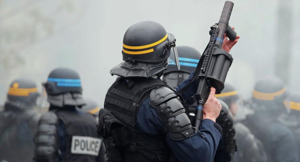 Офицер ОМОНа держит пусковую установку со слезоточивым газом во время демонстрации по случаю первой годовщины движения желтых жилетов в Париже. Франция, 16 ноября 2019 года