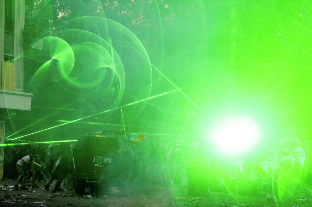 Демонстранты используют лазеры против полиции во время антиправительственных акций в Сантьяго (Чили)