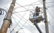 Сотрудник муниципальной службы во время работы с линиями электропередач. Архивное фото