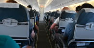 Пассажиры в салоне самолета во время полета.