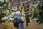 Девушка фотографирует выпавший снег в сквере. Архивное фото