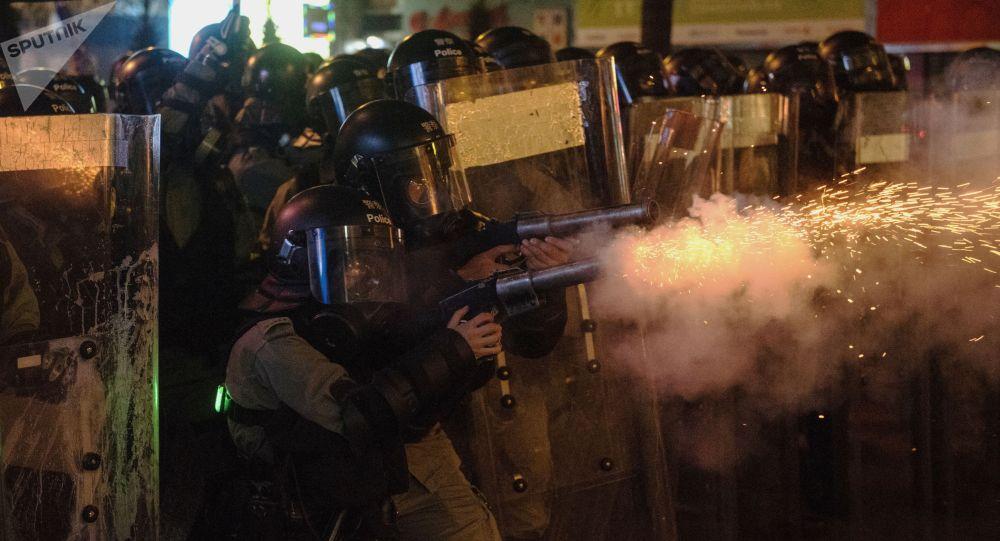 Сотрудники полиции обстреливают антиправительственных демонстрантов слезоточивым газом в Гонконге.