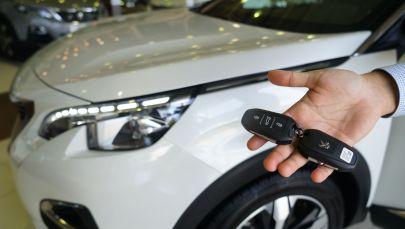 Сотрудник держит ключи от автомобиля в автосалоне. Архивное фото