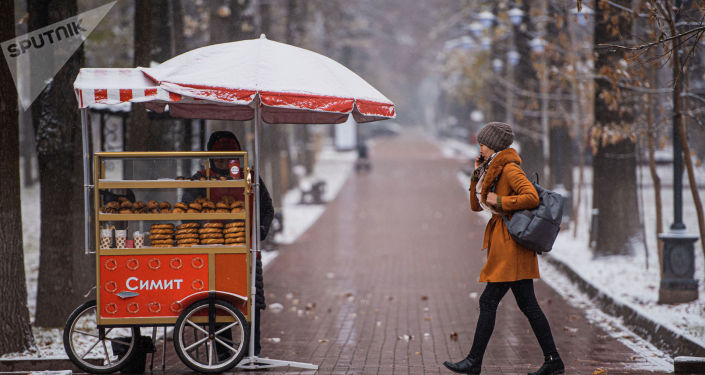 Девушка идет по бульвару Эркиндик во время снегопада в Бишкеке