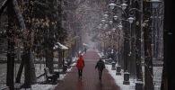 Люди идут по бульвару Эркиндик во время снегопада в Бишкеке