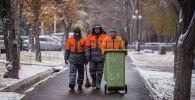Сотрудники МП Тазалык идут по тротуару во время снегопада в Бишкеке