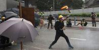 Участник протестов в Гонконге бросает в сторону полиции бутылку с зажигательной смесью.