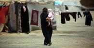 Баласын көтөрүп бараткан Сириялык аял. Архив