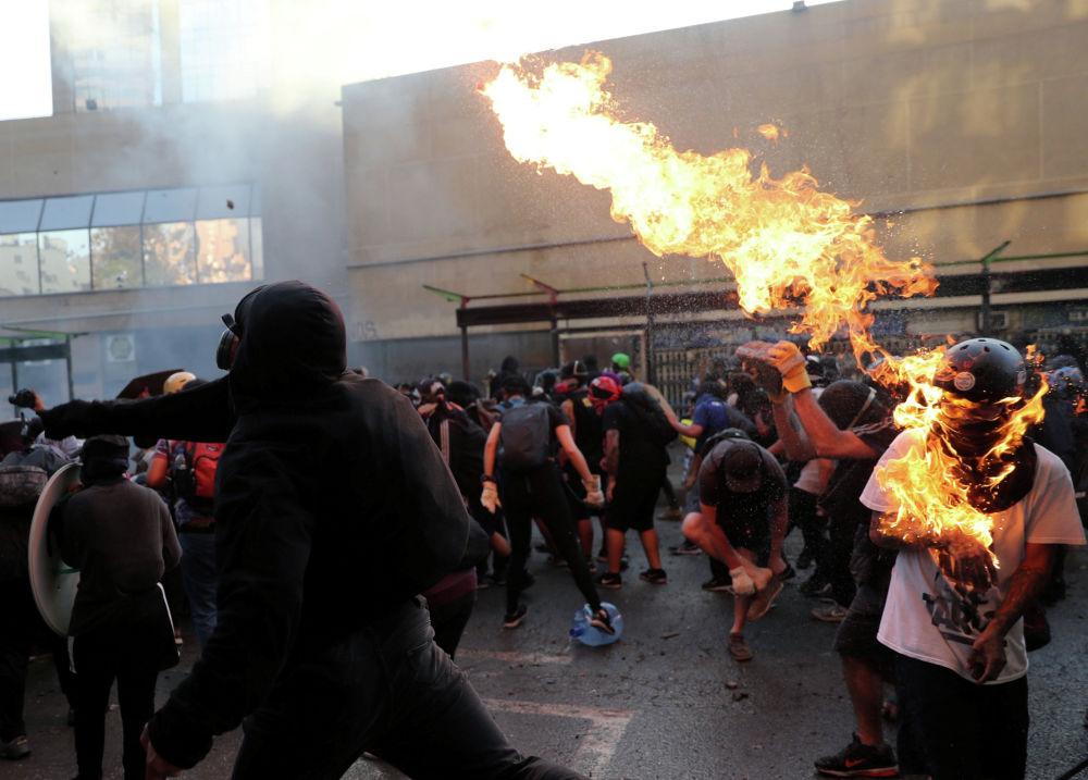 Жесткие столкновения между демонстрантами и полицией продолжаются в столице Чили. Накануне президент Себастьян Пиньера пообещал проведение ряда реформ, в том числе повышение минимальной заработной платы и пенсий, однако манифестации продолжились.