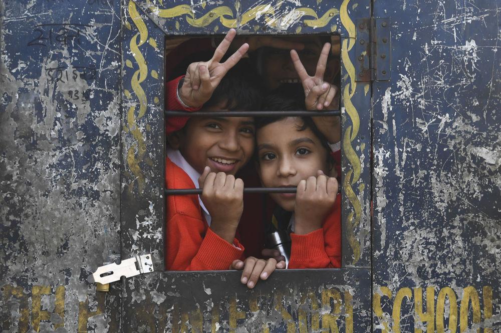 Школьники выглядывают в окно повозки велорикши в старых кварталах Нью-Дели.