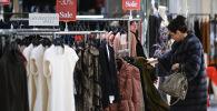 Женщина выбирает одежду во время зимней распродажи в магазине. Архивное фото