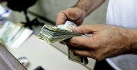 Кассир подсчитывает доллары. Архивное фото