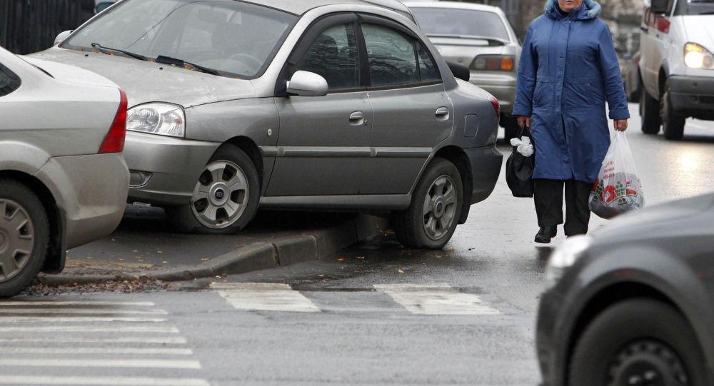 Женщина, идущая по проезжей части вдоль тротуара, который занят припаркованными автомобилями. Архивное фото