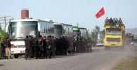 Жители сел Тамга и Борскоон в кузове самосвала (справа) и представители правоохранительных органов (слева) во время беспорядков неподалеку от рудника Кумтор к востоку от Бишкека. Архивное фото