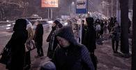 Люди в ожидании общественного транспорта на остановке по улице Киевской в Бишкеке. Архивное фото