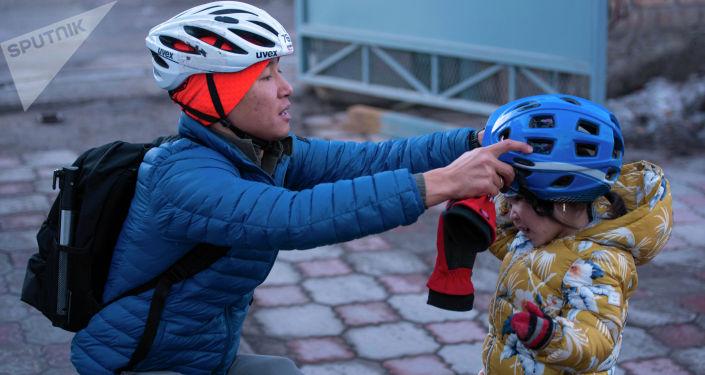 Бишкекчанин Нуршат Абакиров одевает своей дочке велосипедную каску
