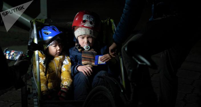 Дети бишкекчанина Нуршата Абакирова в люльке велосипеда