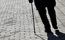 Пожилой мужчина с тростью идет по улице. Архивное фото