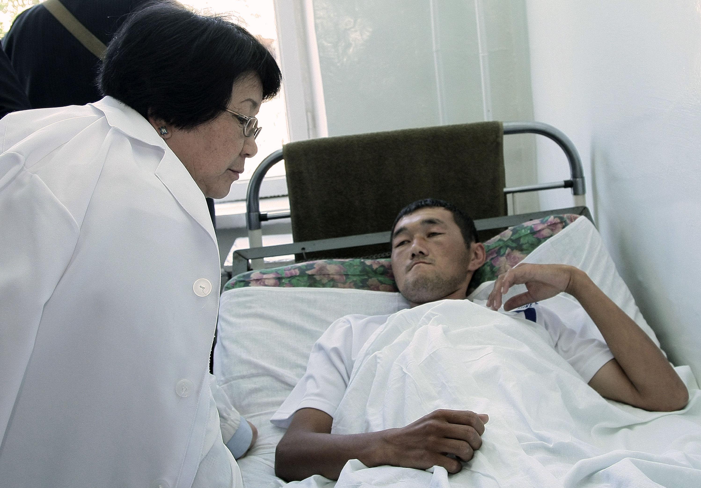 Глава временного правительства Роза Отунбаева беседует с раненым гражданином Кыргызстана в южном городе Ош.