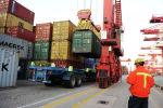 Работник порта, следящий за разгрузкой контейнеров на грузовиках в порту Циндао в провинции Шаньдун на северо-востоке Китая. 7 ноября 2012 года