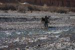 Мальчик нагружает осла бидоном с водой у речки в Баткенской области