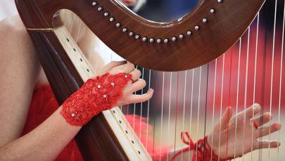 Музыкант играет на арфе. Архивное фото