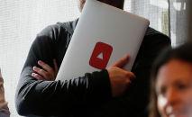 Мужчина держит ноутбук с логотипом YouTube. Архивное фото