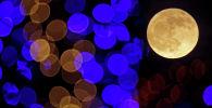 Полная луна на фоне огней. Архивное фото