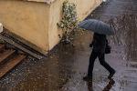 Мужчина с зонтом идет по тротуару во время снегопада в Бишкеке. Архивное фото