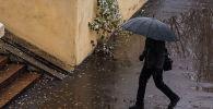 Мужчина с зонтом идет по тротуару во время снегопада в Бишкеке