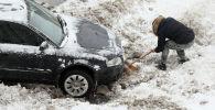 Водитель откапывает из снега свою машину на улице в Москве после снегопада.