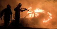 Пожарные тушат пожар в машине. Архивное фото