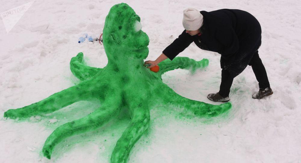 Женщина красит фигуру снежного осьминога. Архивное фото