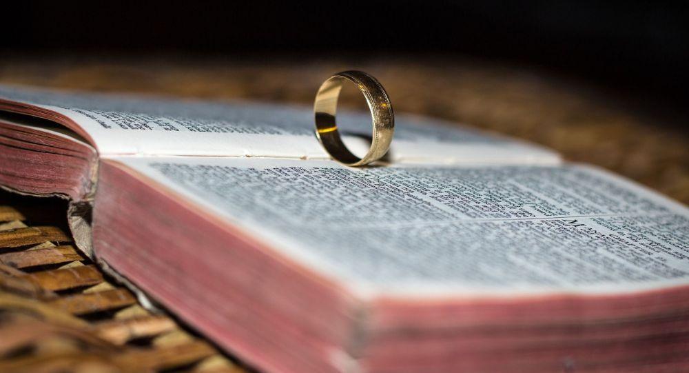 Обручальное кольцо на книге. Архивное фото