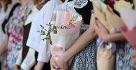 Цветы в руках школьников во время последнего звонка. Архивное фото