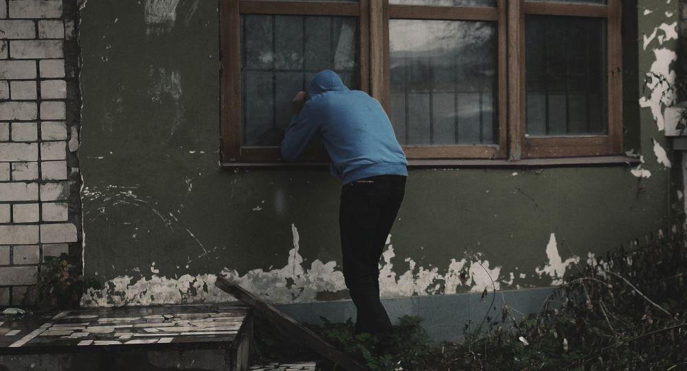Мужчина смотрит в окно частного дома. Архивное фото