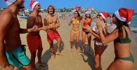 Туристы в рождественских костюмах на пляже в Сиднее (Австралия)
