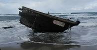 Часть деревянной лодки с останками людей, предположительно из Северной Кореи, видна вдоль берега острова Садо, префектура Ниигата. Япония, 28 декабря 2019 года
