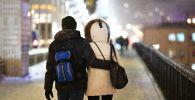 Прохожие на одной из улиц во время снегопада. Архивное фото