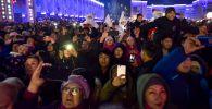Люди снимают на телефоны праздничный салют на центральной площади Ала-Тоо 31 декабря 2019 года