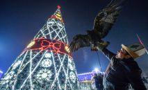 Мужчина держит беркута возле главной елки на площади Ала-Тоо в Бишкеке. Архивное фото