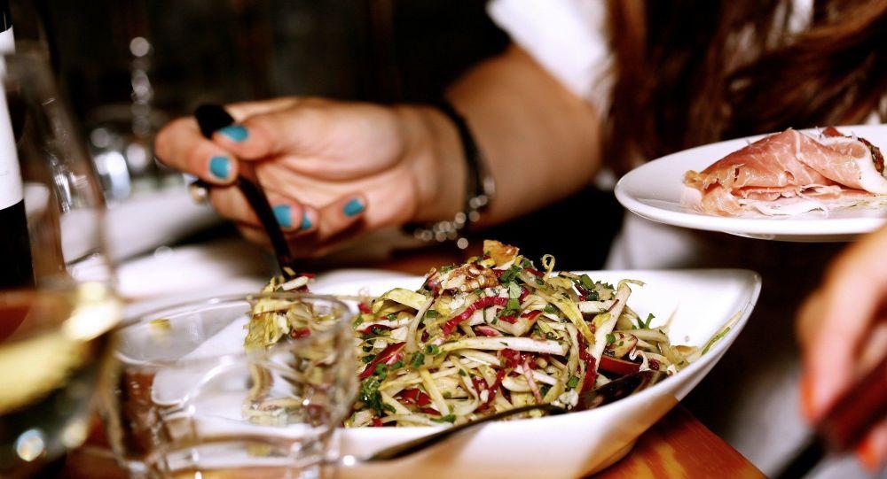 Девушка накладывает еду в тарелку. Архивное фото